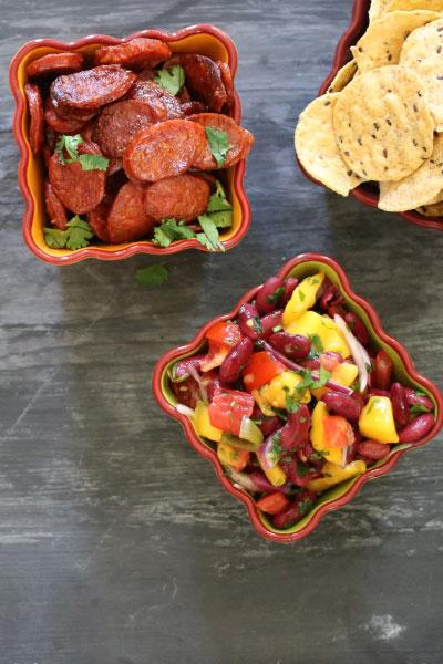Nachos with bean and mango salsa and fried chorizo