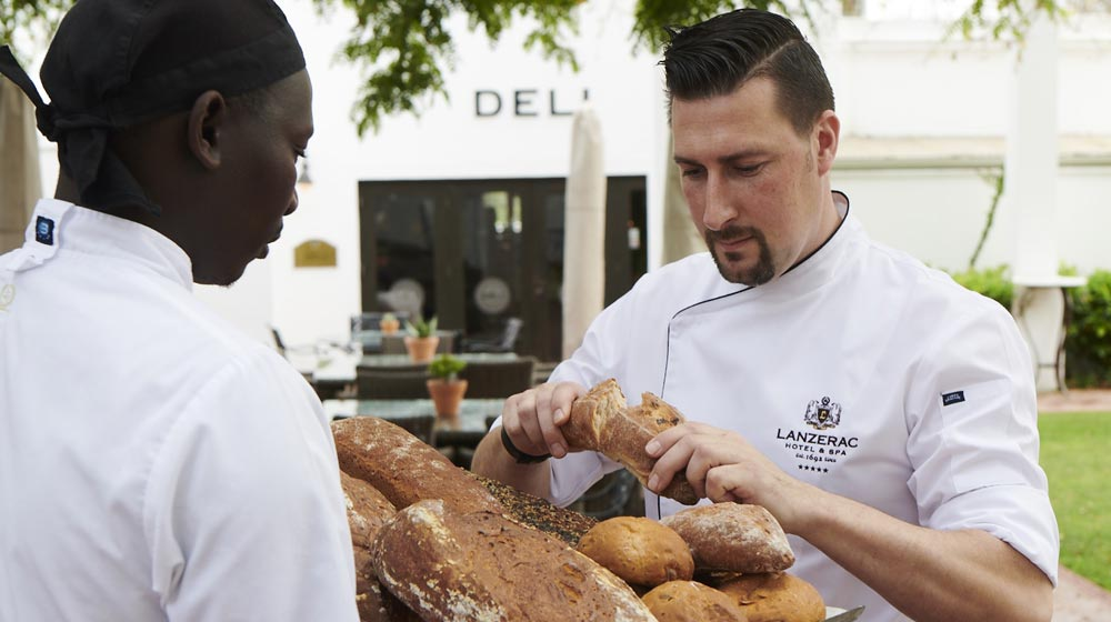 executive chef, Stephen Fraser at Lanzerac, checking quality of bakery's bread
